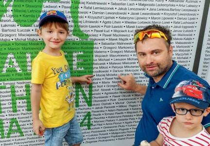 Przed startem. Dr Maciej Mrówka z synami przed tablicą z nazwiskami uczestników triathlonu w Gdyni.